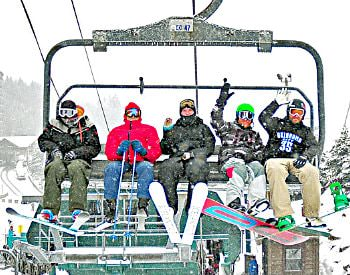 Five people sitting on a ski lift waving, surrounding by thick white snow fall.