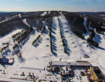 Wide angle view of a ski resort, covered in sparkling white snow and hundreds of pine trees