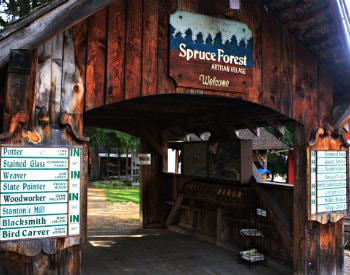 "Exterior view of a brown bridge covering with a blue sign that reads ""Spruce forest artisan village"""