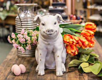 A stone pig sculpture sitting on a brown wooden table surrounded by flower bouquets and 3 eggs