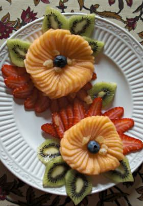 A meticulously cut fruit spread with vibrant orange cantaloupe, strawberries, kiwi, and blueberries