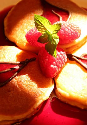 A close up of a breakfast spread, raspberries and syrup covering a stack of fresh golden pancakes.
