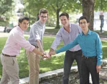 A group of young men dressed in nice dress slacks, different colored button downs, their hands together in the middle.